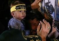 فرزند شهید حججی مقابل تابوت پدر