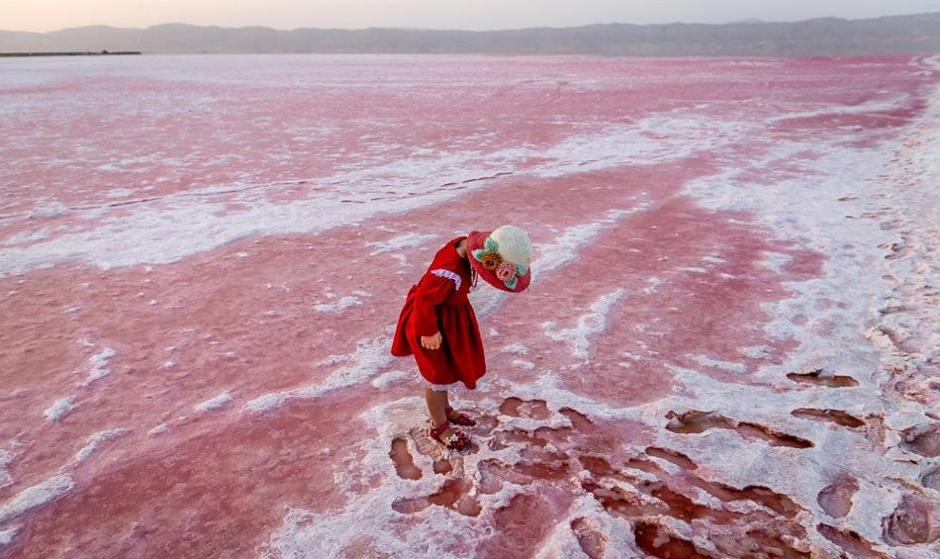 In Pictures: The Little Girl in Red Enjoying the Pink Lake Near Shiraz