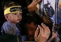 (تصاویر) فرزند شهید حججی مقابل تابوت پدر