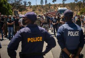 South African white farmers and rival black protesters face off outside court hearing over farm ...